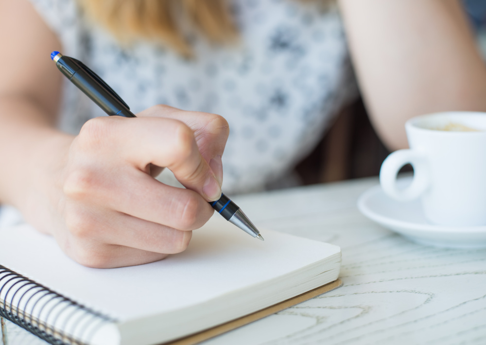 businesswoman with a note-book in a cafe drinking coffee
