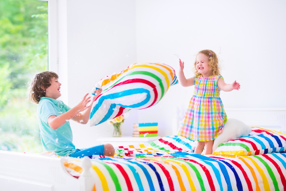 Two children, happy laughing boy and cute curly little girl having fun at pillow fight with feathers in the air jumping, laughing and giggling in a white bedroom with colorful bedding
